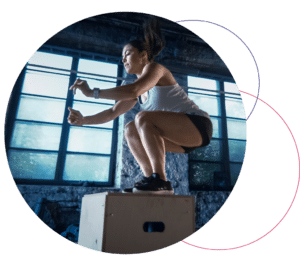 woman jumping on a box in a fitness center